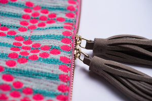 Shows two zippers and tassel attachment of Kavya Clutch Aqua.  This clutch is rectangular with a zip closer and two leather beige/off white tassels.  The clutch is made from woven cotton that is white with aqua stripes and has pink circle embroidery that makes a triangle pattern.  This bag supports girls education in India.