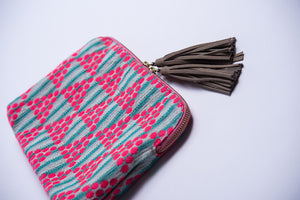 From side angle of Kavya Clutch Aqua.  This clutch is rectangular with a zip closer and two leather beige/off white tassels.  The clutch is made from woven cotton that is white with aqua stripes and has pink circle embroidery that makes a triangle pattern.  This bag supports girls education in India.