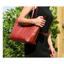 Load image into Gallery viewer, Front of handmade, red tote made from recycled/reclaimed fire hose and reclaimed parachute silk.  Shown over the shoulder of model wearing black dress with red belt.  Had zip top, durable, is water resistant, and fits a laptop.   Perfect for work, carry-on or day bag.