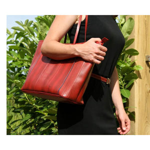 Front of handmade, red tote made from recycled/reclaimed fire hose and reclaimed parachute silk.  Shown over the shoulder of model wearing black dress with red belt.  Had zip top, durable, is water resistant, and fits a laptop.   Perfect for work, carry-on or day bag.