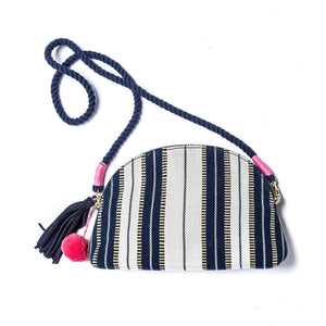 Front of Half Moon Crossbody or clutch is handmade in India and supports girls' education.  It is woven fabric with white and blue stripes and a blue rope strap the is removable.  The bag has a pink pom-pom bag charm and a blue tassel.