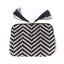 Load image into Gallery viewer, Front of Kavya Clutch Black and Gray.  This clutch supports girls' education in India.  It is rectangular with zip closer and black leather tassels attached to zip closer.  The bag is made of woven cotton fabric with black and gray lines that make a chevron pattern.