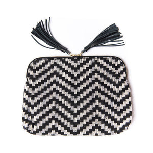 Front of Kavya Clutch Black and Gray.  This clutch supports girls' education in India.  It is rectangular with zip closer and black leather tassels attached to zip closer.  The bag is made of woven cotton fabric with black and gray lines that make a chevron pattern.