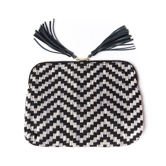 Front of Kavya Clutch Black and Gray.  This clutch supports girls education in India.  It is rectangular with zip closer and black leather tassels attached to zip closer.  The bag is made of woven cotton fabric with black and gray lines that make a chevron patter.
