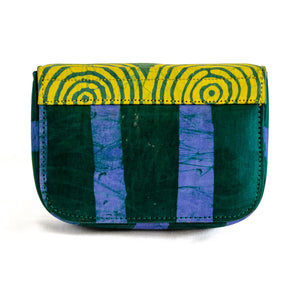 Back of small box bag with split flap front to be used as a clutch or shoulder bag.  Body of bag made with Adire fabric in vertical thick green and blue stripes down front of bag.  The top and split flap closure is made of Adire fabric with a green pattern of circles inside of circles and a yellow background with two magnetic snaps for closure where the split flap touches the front of the bag.
