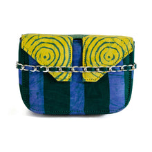 Load image into Gallery viewer, Front of small box bag with split flap front to be used as a clutch or shoulder bag.  Shows chain strap across front with fabric through it.  Body of bag made with Adire fabric in vertical thick green and blue stripes down front of bag.  The top and split flap closure is made of Adire fabric with a green pattern of circles inside of circles and a yellow background with two magnetic snaps for closure where the split flap touches the front of the bag.