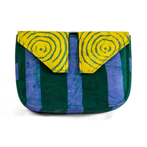 Front of small box bag with split flap front to be used as a clutch or shoulder bag.  Body of bag made with Adire fabric in vertical thick green and blue stripes down front of bag.  The top and split flap closure is made of Adire fabric with a green pattern of circles inside of circles and a yellow background with two magnetic snaps for closure where the split flap touches the front of the bag.