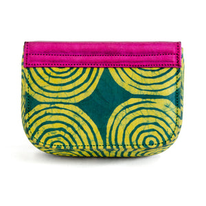 Back of small box bag with split flap front to be used as a clutch or shoulder bag.  Made with yellow and green Adire fabric that shows a pattern of circles inside circles in yellow on green for the body of the bag.  The top and split flap closure is made of metallic pink leather with two magnetic snaps for closure where the split flap touches the front of the bag.