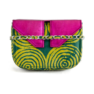 Front of small box bag with split flap front to be used as a clutch or shoulder bag.  This picture shoes chain strap cross front with fabric through it. Made with yellow and green Adire fabric that shows a pattern of circles inside circles in yellow on green for the body of the bag.  The top and split flap closure is made of metallic pink leather with two magnetic snaps for closure where the split flap touches the front of the bag.
