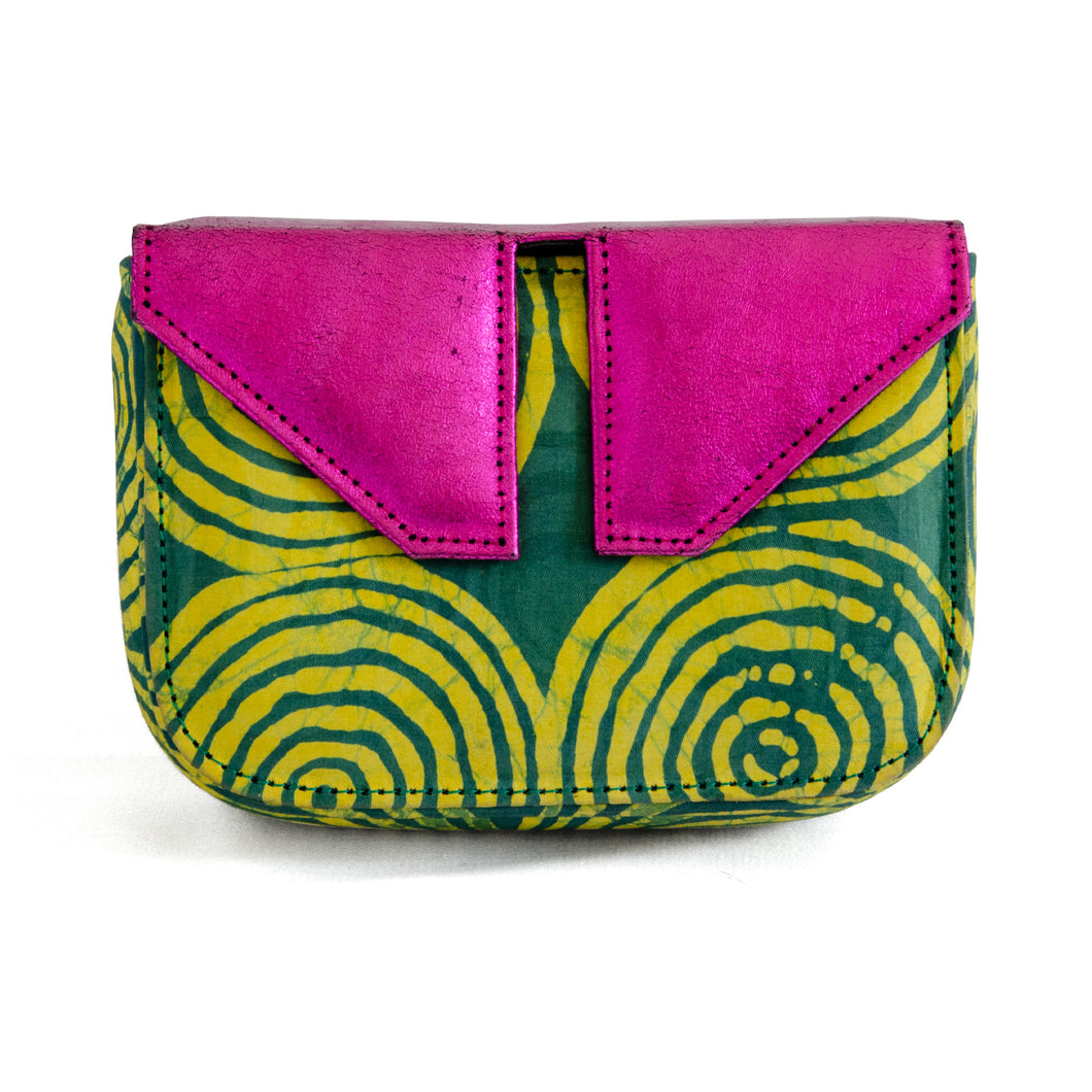 Front of small box bag with split flap front to be used as a clutch or shoulder bag.  Made with yellow and green Adire fabric that shows a pattern of circles inside circles in yellow on green for the body of the bag.  The top and split flap closure is made of metallic pink leather with two magnetic snaps for closure where the split flap touches the front of the bag.