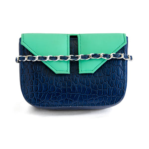 Front of small box bag with split flap front to be used as a clutch or shoulder bag.  This shows front of bag with chain strap around it with dark blue leather through strap.  Made textured dark blue leather for the body of the bag.  The top and split flap closure is made of aqua/teal leather with two magnetic snaps for closure where the split flap touches the front of the bag.