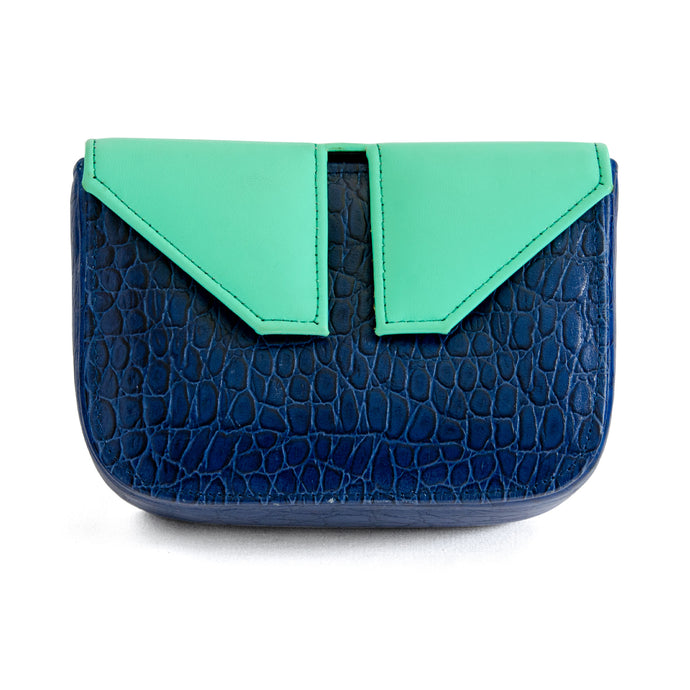 Front of small box bag with split flap front to be used as a clutch or shoulder bag.  Made textured blue leather for the body of the bag.  The top and split flap closure is made of aqua/teal leather with two magnetic snaps for closure where the split flap touches the front of the bag.
