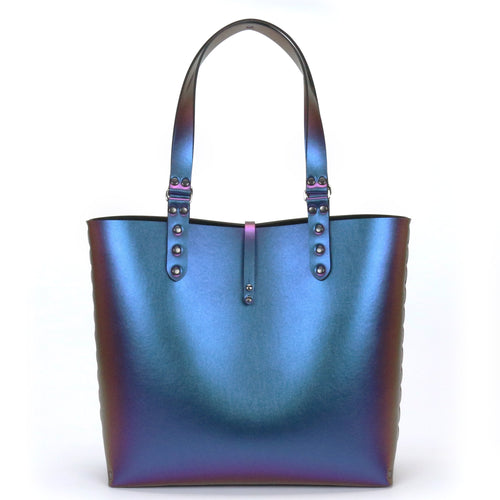 Peacock blue iridescent, vegan tote.  Front of tote with handles to be carried by hand or over the shoulder.  Has a thin strap of fabric that button from back to front to secure bag closed.  Sides handles are hand riveted together.