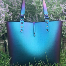 Load image into Gallery viewer, Peacock blue iridescent, vegan tote.  Front of tote with handles to be carried by hand or over the shoulder.  Has a thin strap of fabric that button from back to front to secure bag closed.  Sides handles are hand riveted together.
