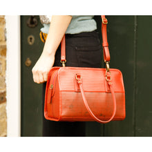 "Load image into Gallery viewer, Hand made red ""Post Bag"" purse/handbag made from reclaimed fire hose and parachute silk.  Two handles and zipper top with one interior zip pocket.  Comes with long adjustable and removable strap to carry as a crossbody.  Bag is durable and water resistant.  Shown worn as crossbody from hip of model."