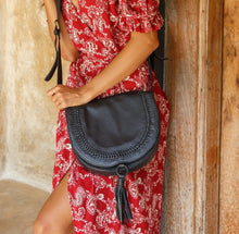 Load image into Gallery viewer, Structures crossbody saddle bag in red leather with snap closer and hoop with red leather tassel hanging off bottom.  Front has detail of woven leather in line just in from edge of front flap.  Worn as crossbody on model with red dress with white outlined flower pattern.