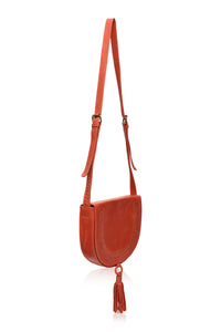Structures crossbody saddle bag in red leather with snap closer and hoop with red leather tassel hanging off bottom.  Front has detail of woven leather in line just in from edge of front flap.