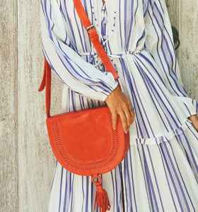 Structures crossbody saddle bag in red leather with snap closer and hoop with red leather tassel hanging off bottom.  Front has detail of woven leather in line just in from edge of front flap.  Shown over shoulder of model with white and blue stripped dress.