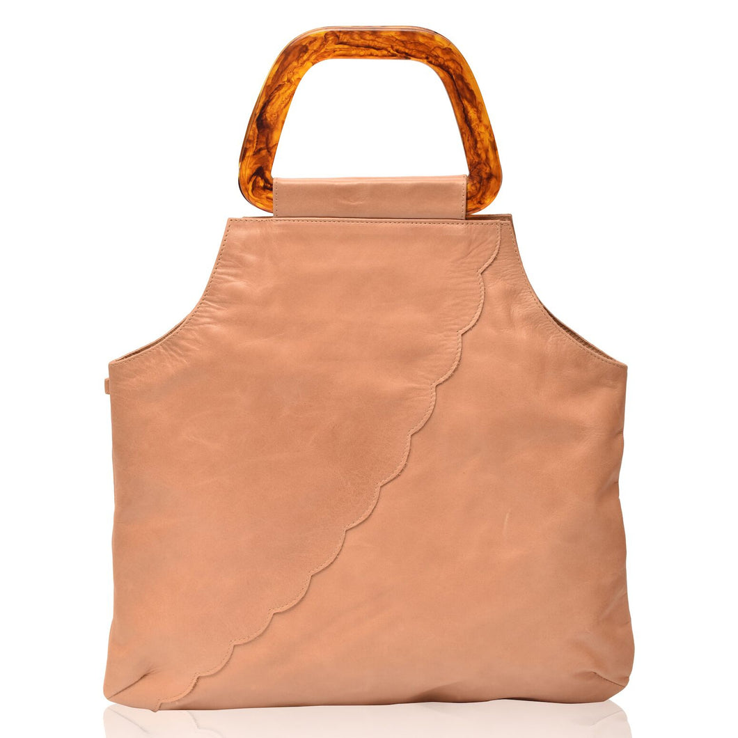 Surreal beige leather handbag with scalloped pattern across front at a diagonal and resin handles.  Bottom of bag is rectangular then bag comes up and cuts into the sides to top where handles are attached.