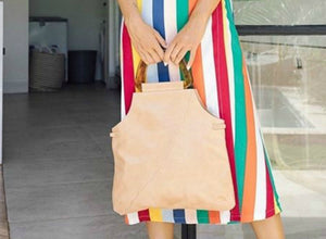 Surreal beige leather handbag with scalloped pattern across front at a diagonal and resin handles.  Bottom of bag is rectangular then bag comes up and cuts into the sides to top where handles are attached.  Bag pictured held in front of model by handles.  Model in vertical colorful striped dress.