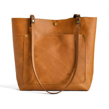 Load image into Gallery viewer, Classic leather tote from front.  Honey colored leather with front pocket and button closure