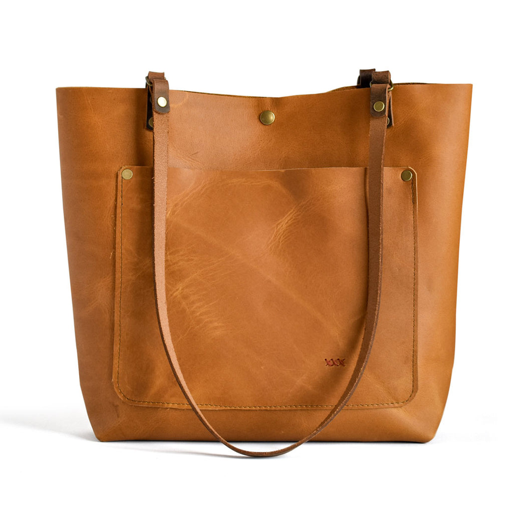Classic leather tote from front.  Honey colored leather with front pocket and button closure