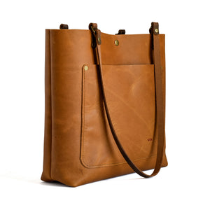 Classic leather tote from side.  Honey colored leather with front pocket and button closure