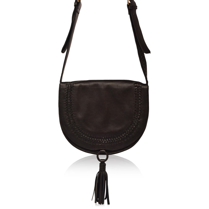 Structures crossbody saddle bag in black leather with snap closer and hoop with black leather tassel hanging off bottom.  Front has detail of woven leather in line just in from edge of front flap.