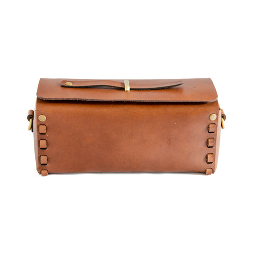 Front of Brown leather box bag.  Rectangular shaped box bag with edges stitched together with strip of leather on either end.  Top folds over with metal loop through top and leather strip through it to close bag.  Comes with detachable strap to be carried as a crossbody or clutch.
