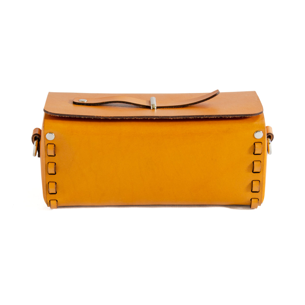 Front of Tan/Yellow leather box bag.  Rectangular shaped box bag with edges stitched together with strip of leather on either end.  Top folds over with metal loop through top and leather strip through it to close bag.  Comes with detachable strap to be carried as a crossbody or clutch.