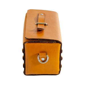 End of Tan/Yellow leather box bag.  Rectangular shaped box bag with edges stitched together with strip of leather on either end.  Top folds over with metal loop through top and leather strip through it to close bag.  Comes with detachable strap to be carried as a crossbody or clutch.