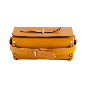 Front of Tan/Yellow leather box bag showing adjustable strap.  Rectangular shaped box bag with edges stitched together with strip of leather on either end.  Top folds over with metal loop through top and leather strip through it to close bag.  Comes with detachable strap to be carried as a crossbody or clutch.