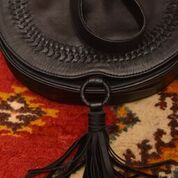 Load image into Gallery viewer, Structures crossbody saddle bag in black leather with snap closer and hoop with black leather tassel hanging off bottom.  Front has detail of woven leather in line just in from edge of front flap.  This picture shows tassel area of bag over colorful rug.