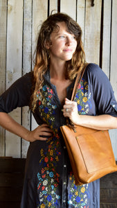 Classic leather tote from the side.  Tote over the should of model in blue and flower dress.  Honey colored leather with front pocket and button closure