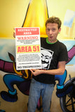 "guy holding area 51 warning sign restricted area 13"" by 22"" vintage style show print poster for size reference in front of a colorful wall painting on a squid man"