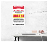 "area 51 warning sign restricted area 13"" by 22"" vintage style show print poster being displayed on a wall by a desk"