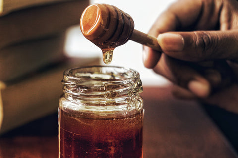 Delicious and skin detoxifying honey in a jar with a honey comb