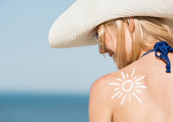 Woman at the beach wearing a hat with sunscreen on