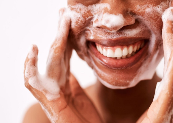 woman cleansing her face with a foaming cleanser