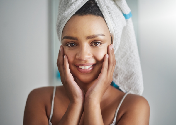 Woman with hair wrapped in a towel, touching her hands to her face