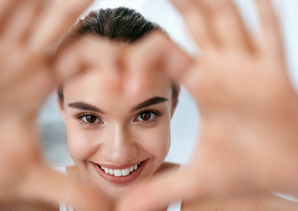 Woman smiling at the camera, making a love heart with her hands