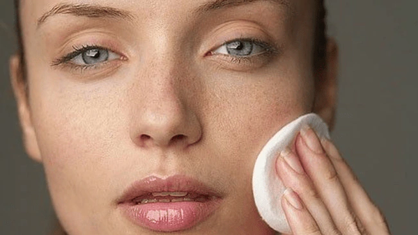 Woman with clean skin removing makeup with a cotton round