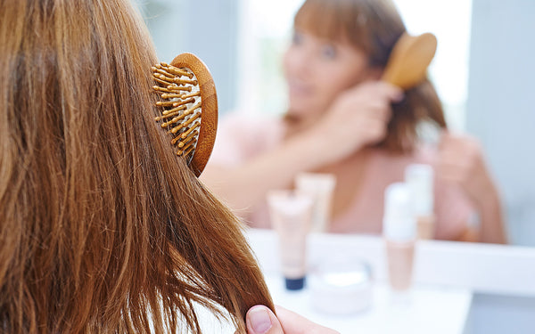 Woman worried about hair loss brushing her hair and looking in the mirror
