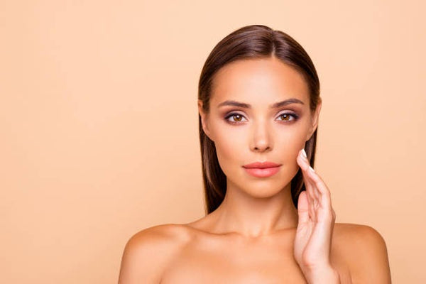 Woman with no facial lines after botox and microneedling touching face