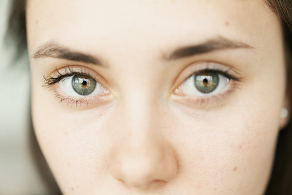Young Woman with clean clear skin uses skincare to get rid of fine lines and wrinkles around the crows feet
