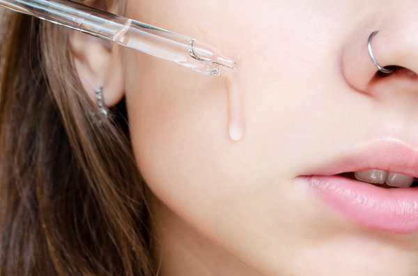Close up of a young woman applying a hydrating skincare serum to a cleansed face