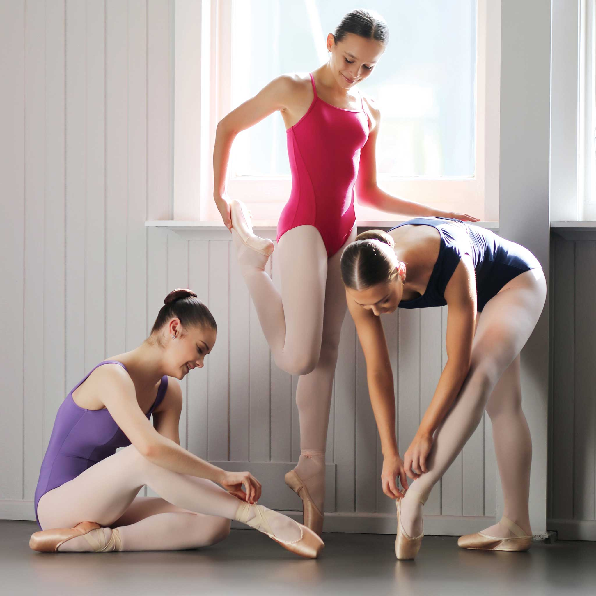 Three dancers putting on pointe shoes and wearing three different dance leotards.