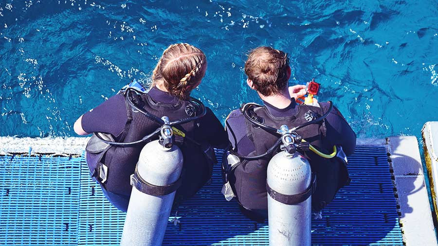 Female Dive Instructor and student on dive boat
