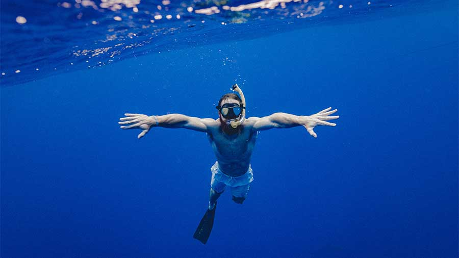 healthy man snorkeling in ocean