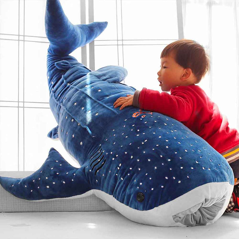 Child playing with big whale shark cuddly toy